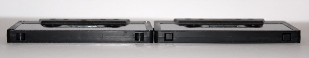 Tab-in and tab-out black cassette shells from Duplication.ca