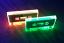 Florescent green and orange cassette tapes under blacklight